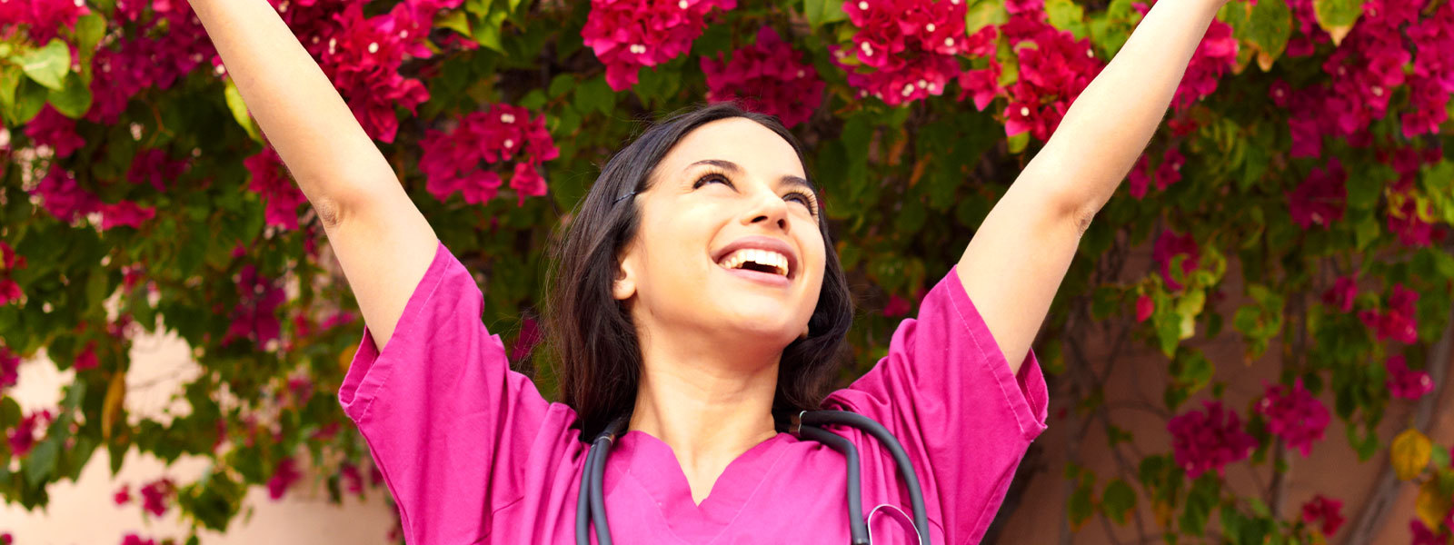 Nursing smiling, wearing bright pink scrubs as she stands in front of flowers.